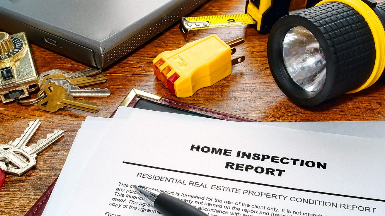 Home inspection report on table with work tools