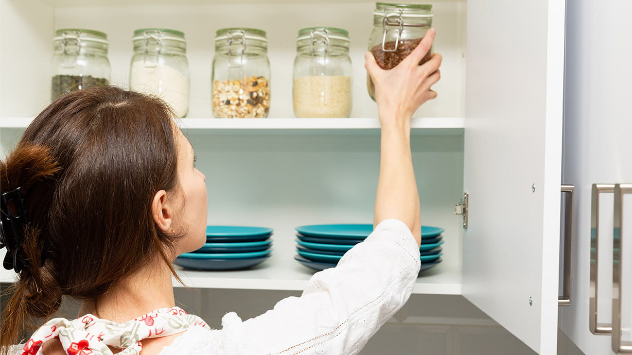 Woman placing jar back in kitchen cabinet