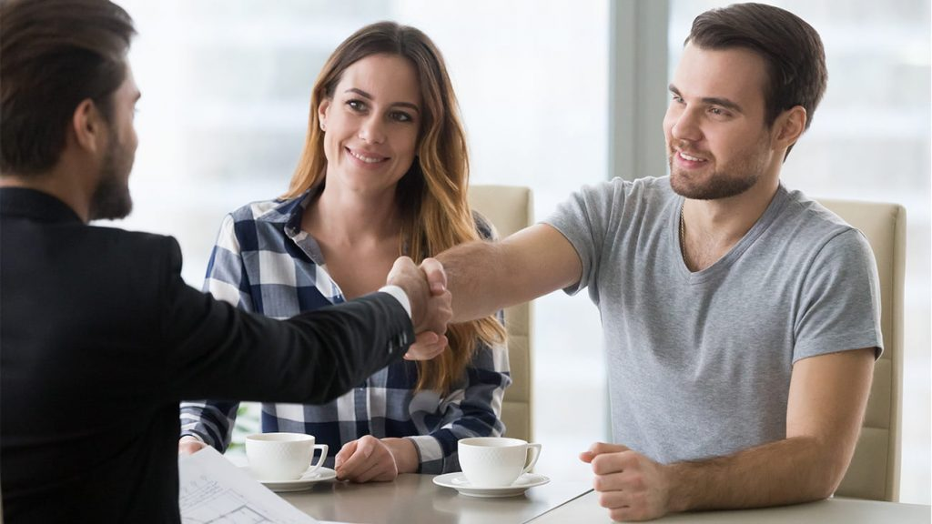 Mortgage lender shakes hands with happy customers