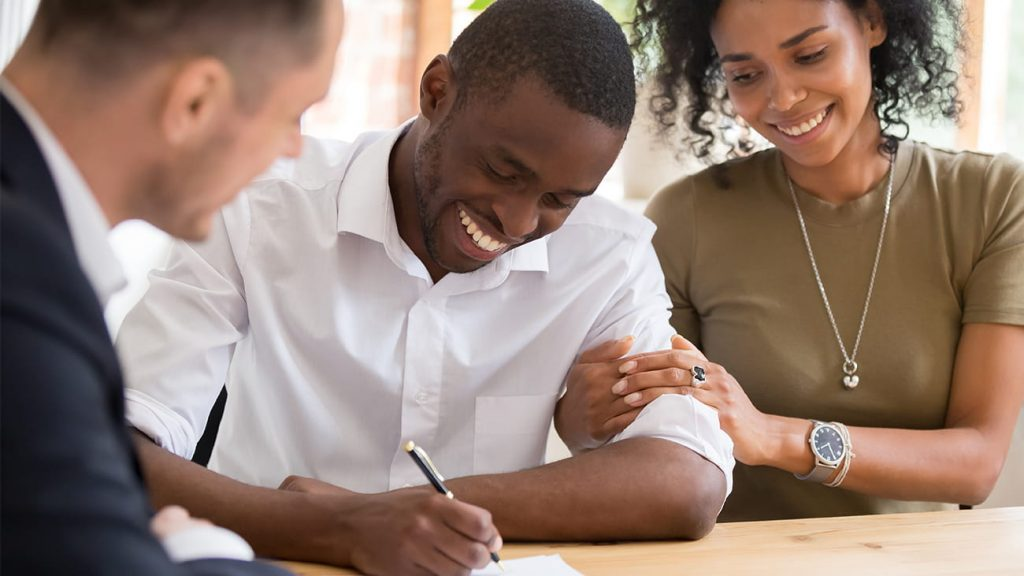 Young couple signing closing documents next to mortgage lender