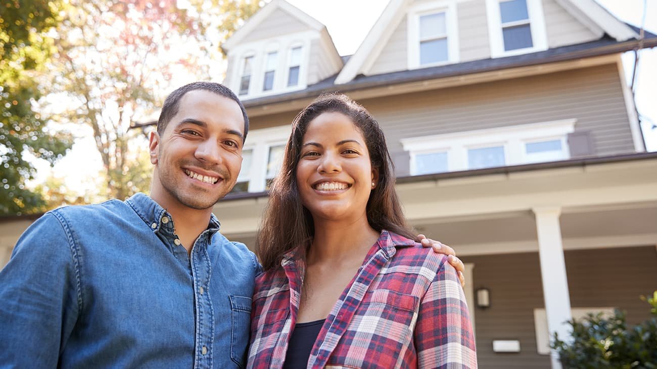 Smiling couple standing at front of house