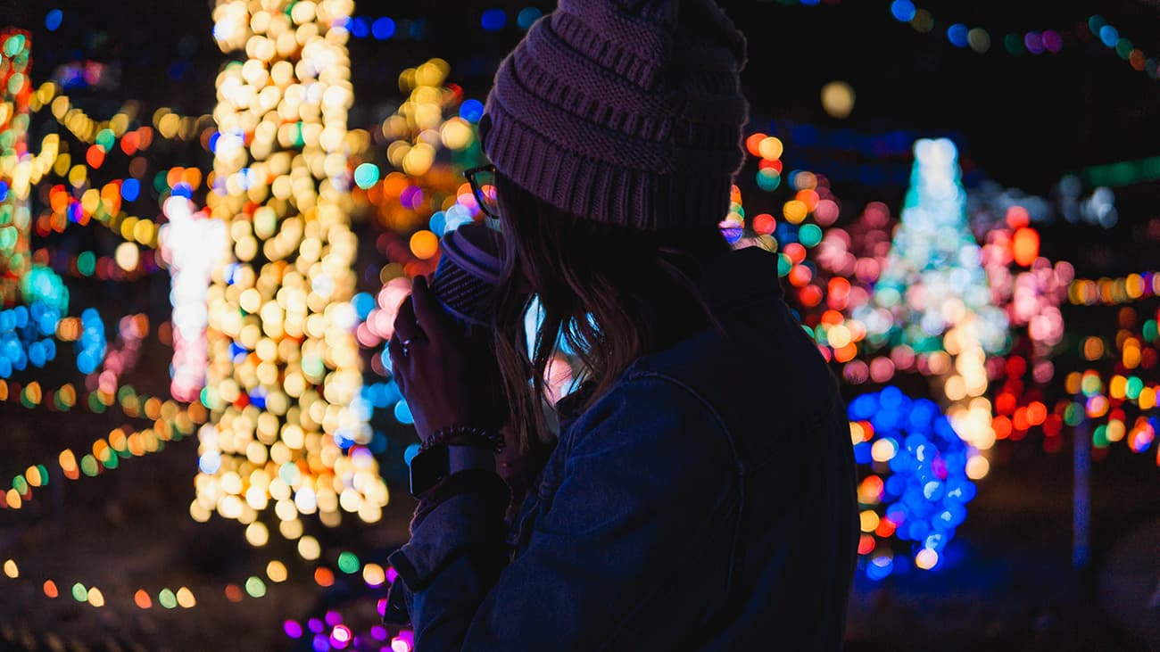Woman sipping coffee and looking at light display