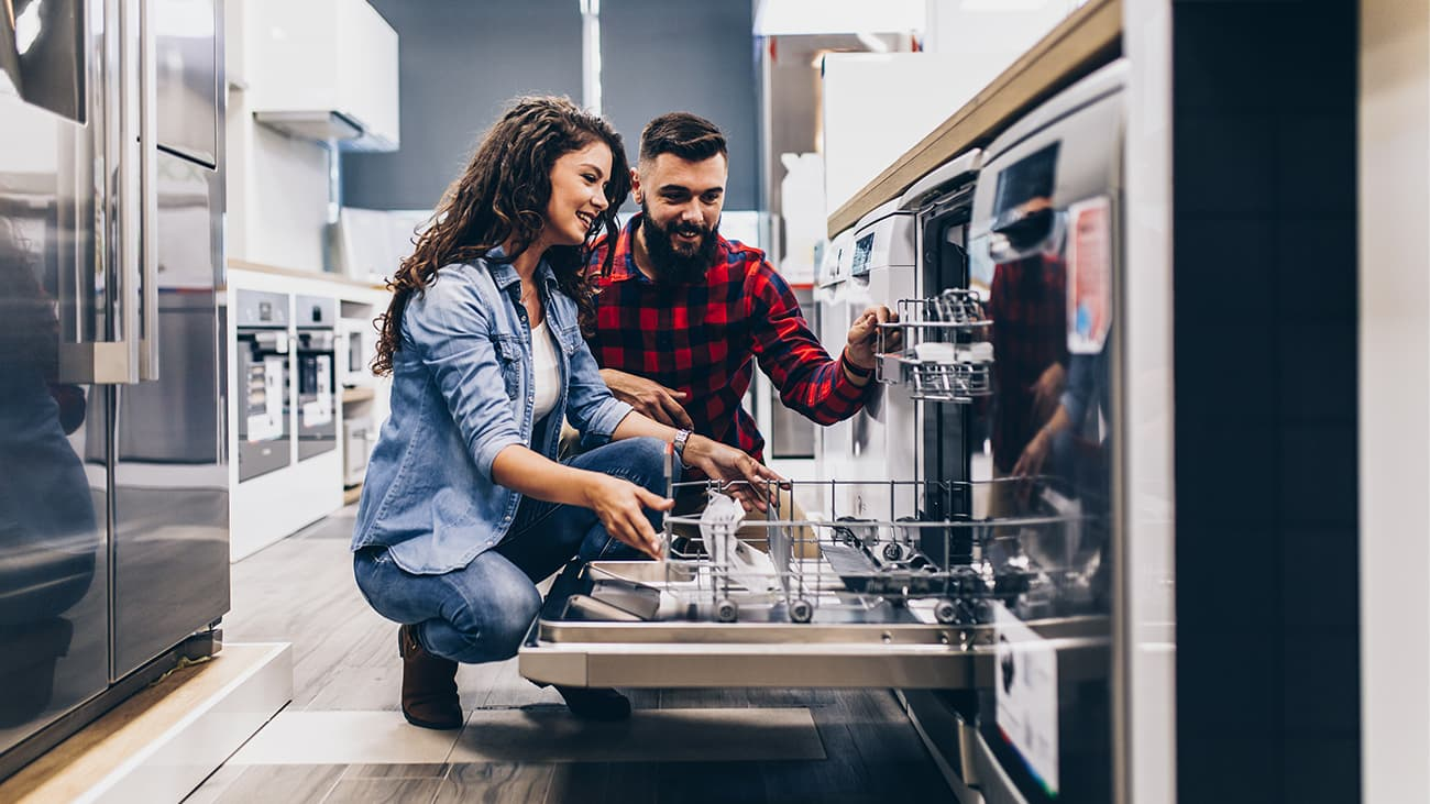 Happy couple looking at dishwasher in appliance store