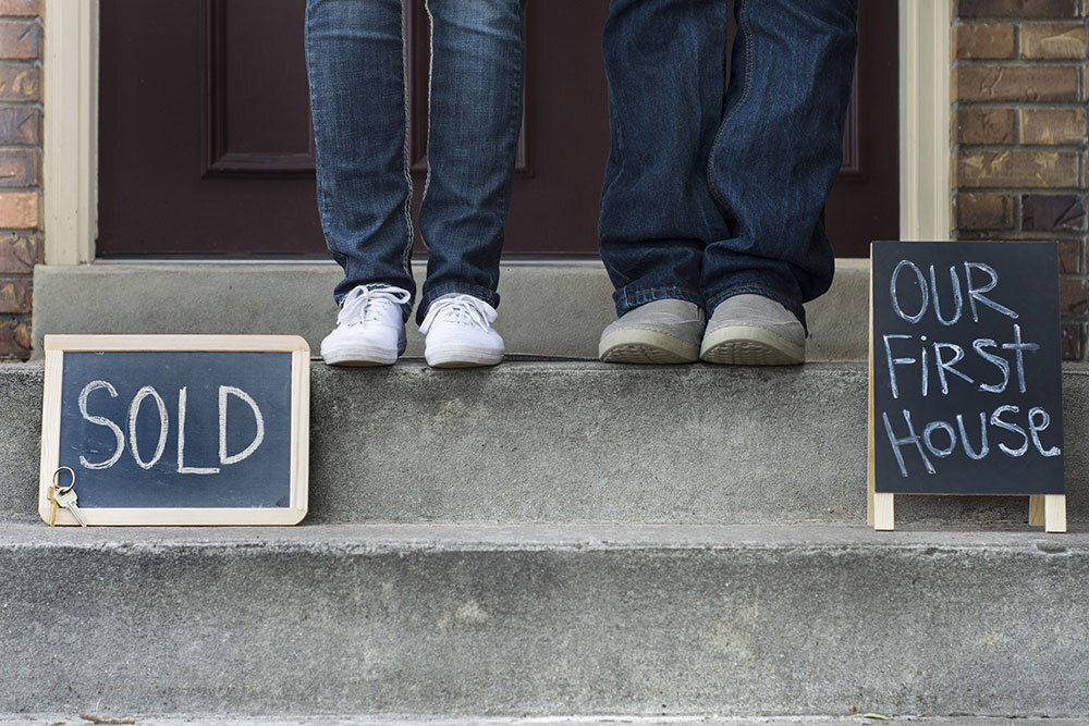 """""""Sold"""" sign and """"Our First House"""" sign on porch steps"""